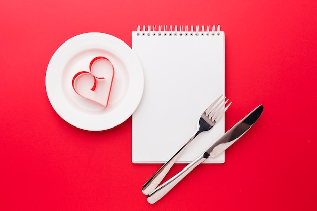 Paper heart shape on plate with notebook for valentines day Free Photo