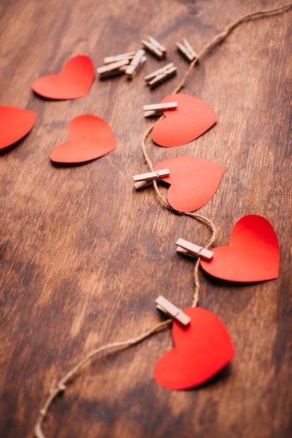 Paper hearts pinned to rope on table Free Photo