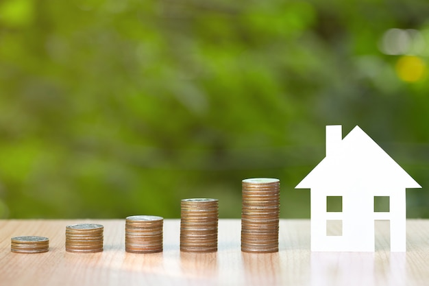 Paper house and coins stack for saving to buy a house Premium Photo