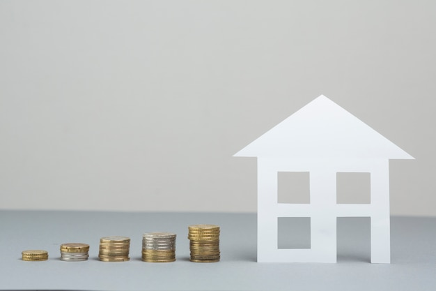 Paper house model with stack of increasing coins on grey surface Free Photo