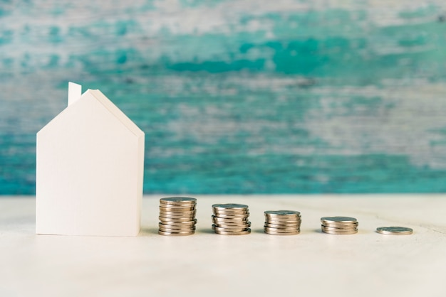 Paper house model with stack of increasing coins on white surface against weathered wall Free Photo