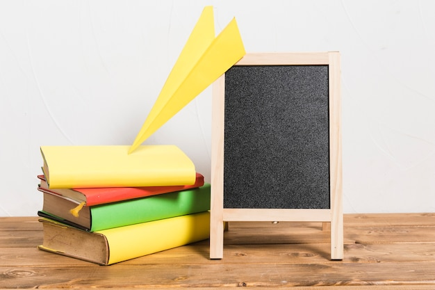 Paper kite on stack of colorful old books and empty blackboard on wooden table Free Photo