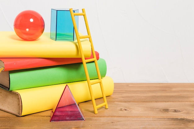 Paper ladder on stack of colorful books and toys Free Photo