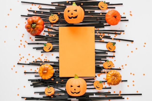 Paper laid on plastic tubes with pumpkins around Free Photo