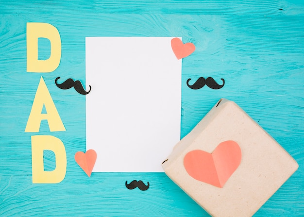 Paper near box with red hearts, mustache and dad title Free Photo