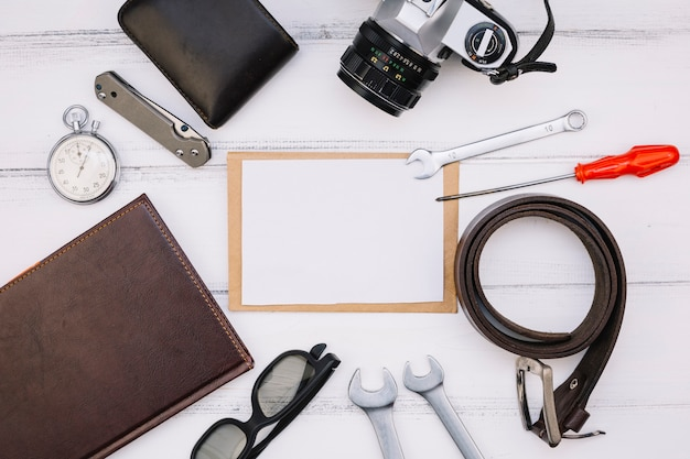 Paper near camera, notebook, stop watch, repair equipments and leather strap Free Photo