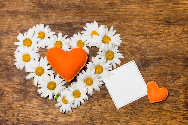 Paper near ornamental heart of white flowers and orange toys Free Photo