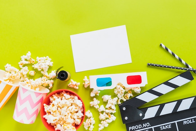 Paper near popcorn, clapboard and 3d glasses Free Photo