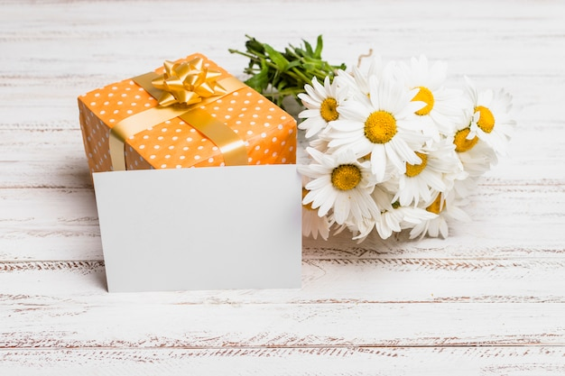 Paper near present box and bunch of flowers Free Photo
