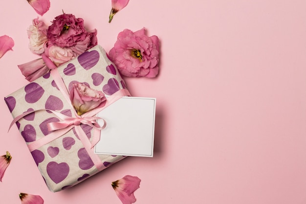 Paper near present and flowers and petals Free Photo