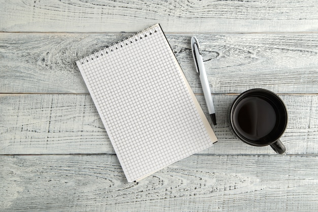 Paper notebook, pen and cup of tea or coffee on vintage shabby white wood, top view Premium Photo