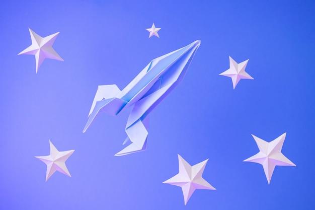 종이 접기 로켓 파란색에 종이 별 사이에서 날아 프리미엄 사진