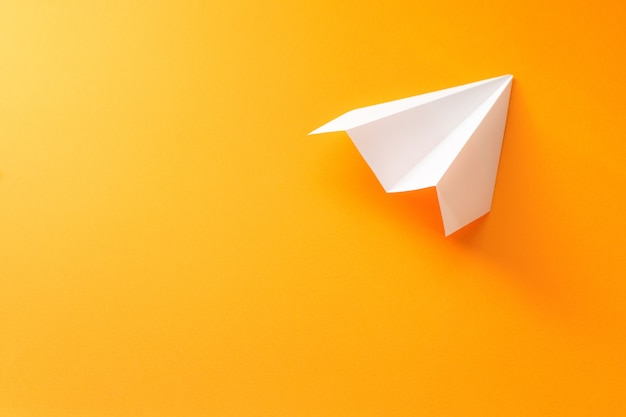 오렌지 배경에 종이 비행기 프리미엄 사진