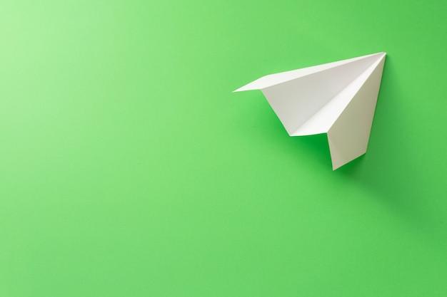 녹색 배경에 종이 비행기 프리미엄 사진