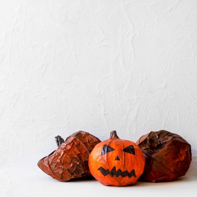 Paper pumpkins near spooky jack-o-lantern Free Photo