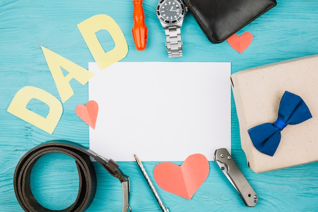 Paper between red hearts and dad title near male accessories Free Photo