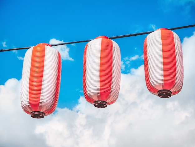 Paper red-white japanese lanterns chochin hanging on blue sky Premium Photo