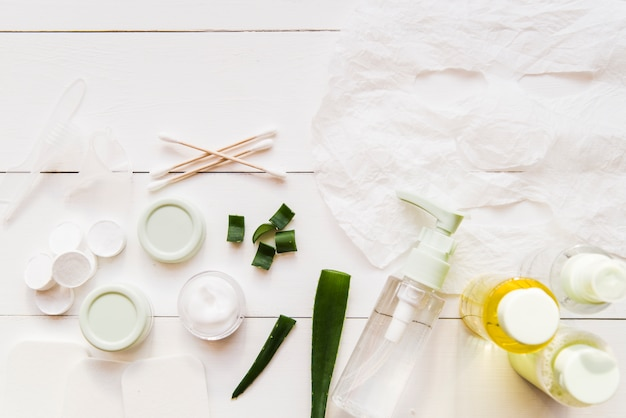 Paper sheet face mask; cotton swabs; moisturizer and aloevera on white wooden plank Free Photo