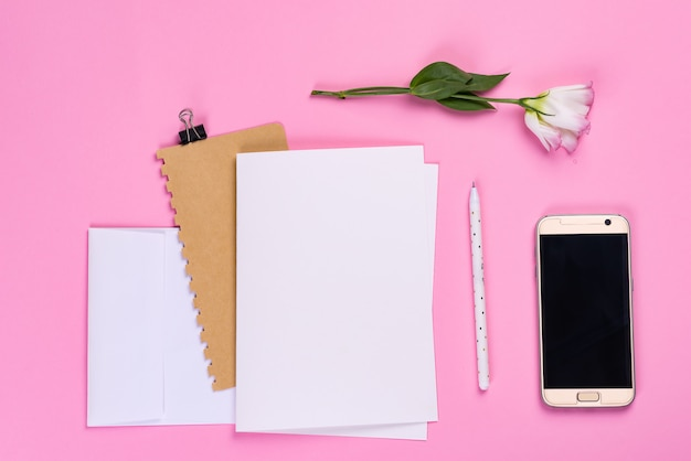 Paper sheets, phone and notebook with eustoma pink flower Premium Photo