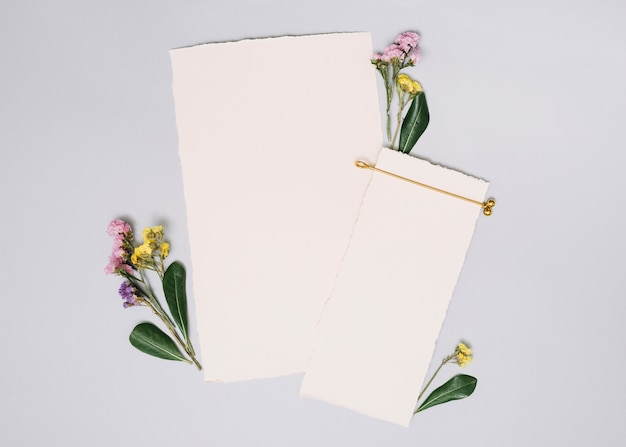 Paper sheets with small branches on white table Free Photo