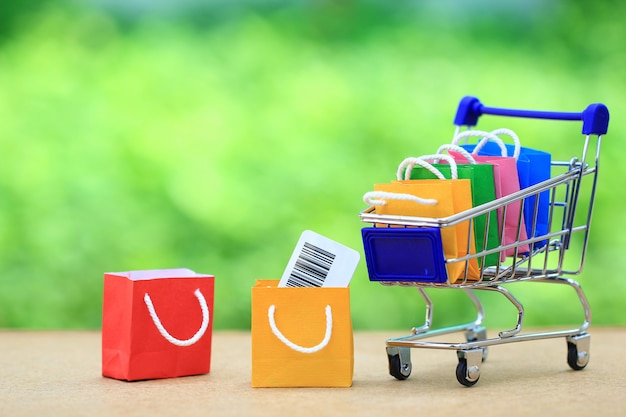 Paper shopping bag on model miniature shopping cart, shopping concept Premium Photo