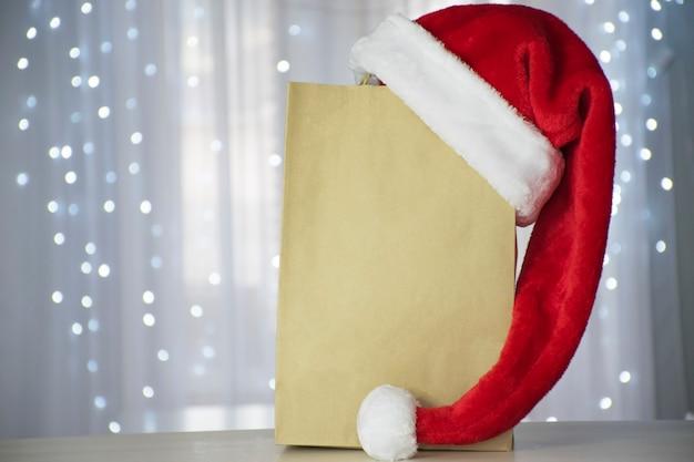 あなたのテストのための場所とクリスマスライト付きのサンタ帽子が付いている紙の買い物袋 Premium写真