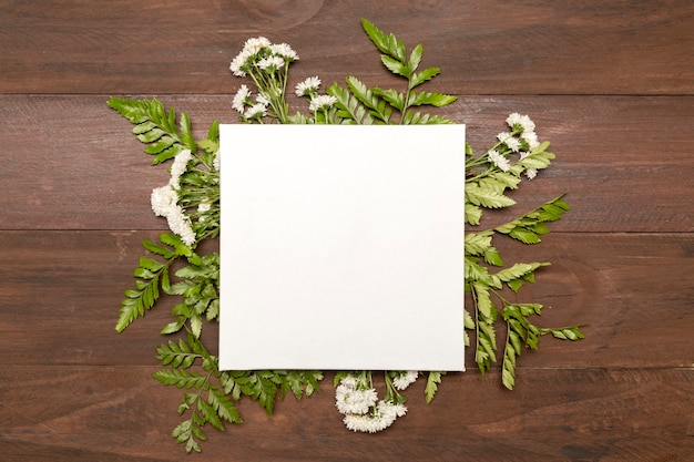 Paper surrounded by green leaves Free Photo
