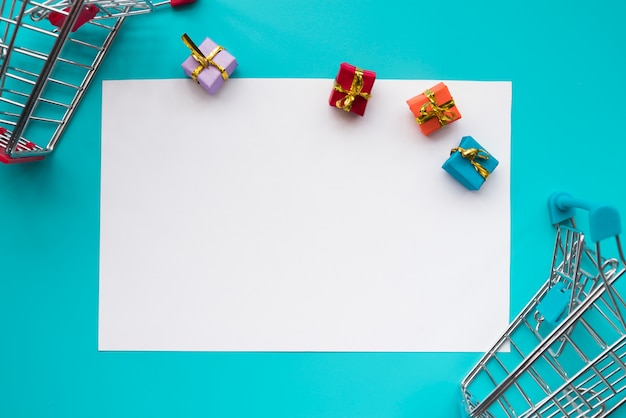 Paper surrounded with mini presents and shopping carts Free Photo