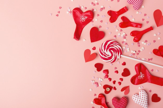 Paper valentines day hearts with sweets on pink Free Photo