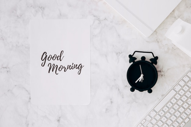 Paper with good morning text; alarm clock; diary; milk carton and keyboard on desk Free Photo