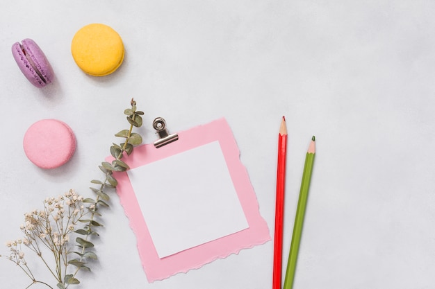 Paper with macaroons and flower branch on table Free Photo