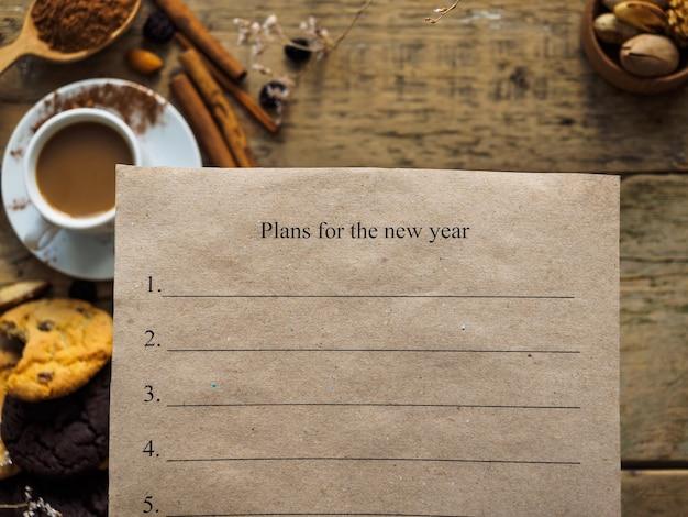 テーブルの上に新年の計画が書かれた紙 Premium写真