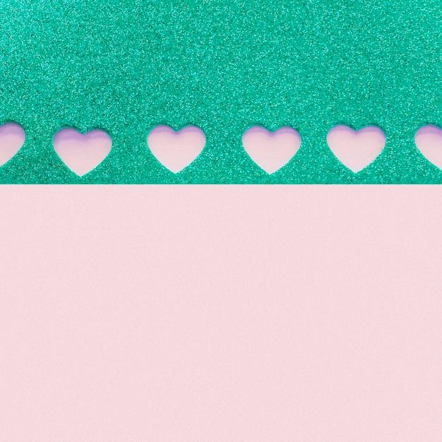 Carta con piccoli cuori tagliati sul tavolo viola Foto Gratuite