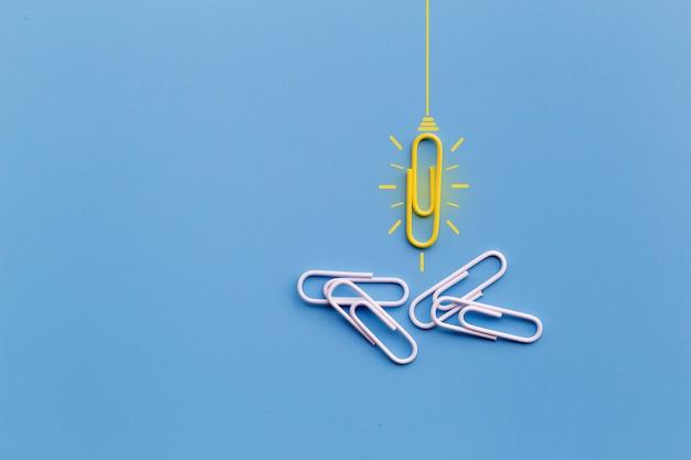 Концепция отличных идей с paperclip, думая, творческими способностями, электрической лампочкой на голубой предпосылке, новой концепцией идей. Premium Фотографии