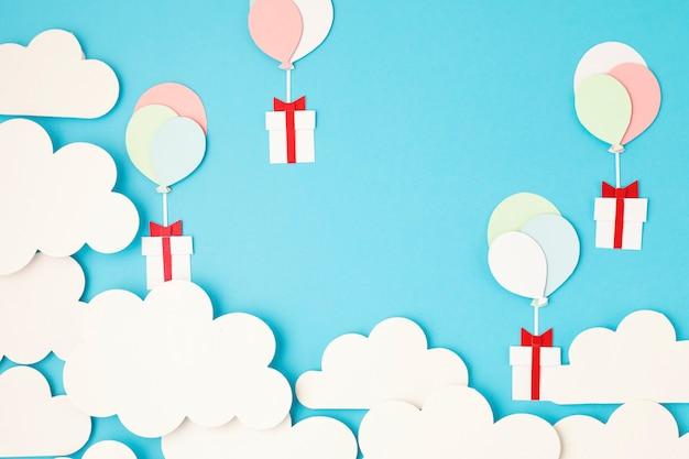 Papercut 풍선과 구름과 푸른 하늘에 떠있는 선물 상자 프리미엄 사진
