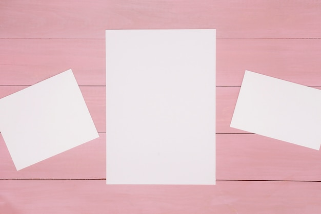 Papers on pink wooden surface Free Photo