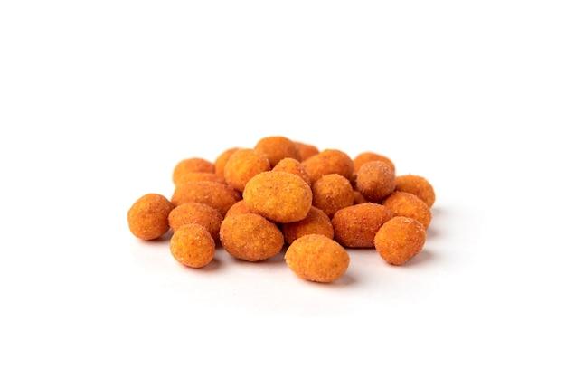 Арахис жареный паприкой изолированный на белой предпосылке. вкусная закуска из арахиса. Premium Фотографии