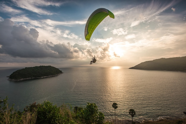 Paraglider chasing the sunset on windmill viewpoint. phuket, thailand. Premium Photo
