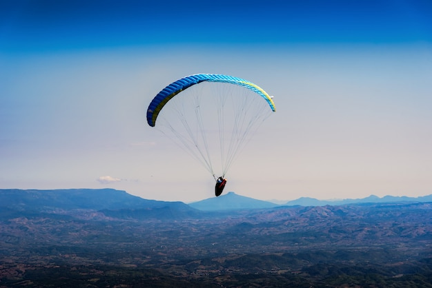 Paraglider flying over mountains in the morning on summer day at north of thailand. Premium Photo