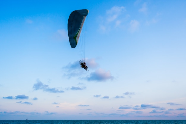 Paraglider flying on sea and sky Premium Photo