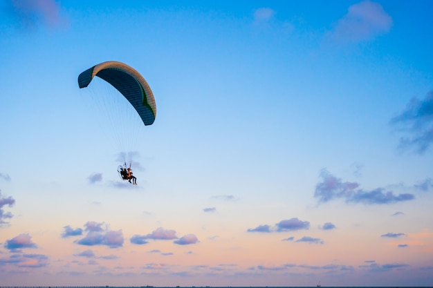Paraglider flying on sky at sunset Premium Photo