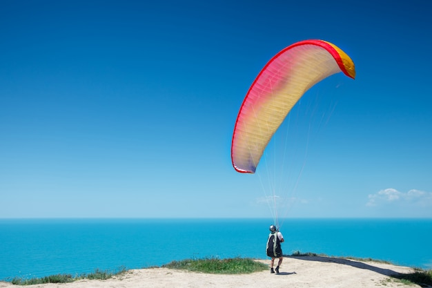Paraglider prepares for flight on a paraplane. beautiful summer background. Premium Photo