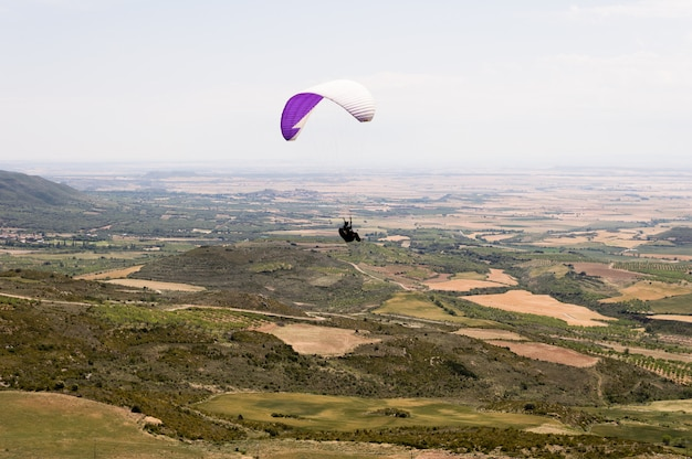 Paraglider silhouette flying over valley in loarre, huesca, spain. Premium Photo