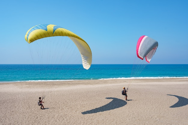 Paraglider tandem flying over the sea shore with blue water and sky on horison. view of paraglider and blue lagoon in turkey. Free Photo