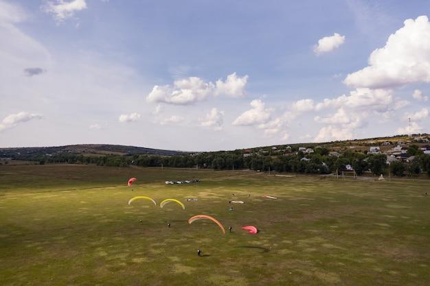 Sagoma di parapendii volando sopra il bellissimo paesaggio verde sotto il cielo blu con nuvole. Foto Gratuite