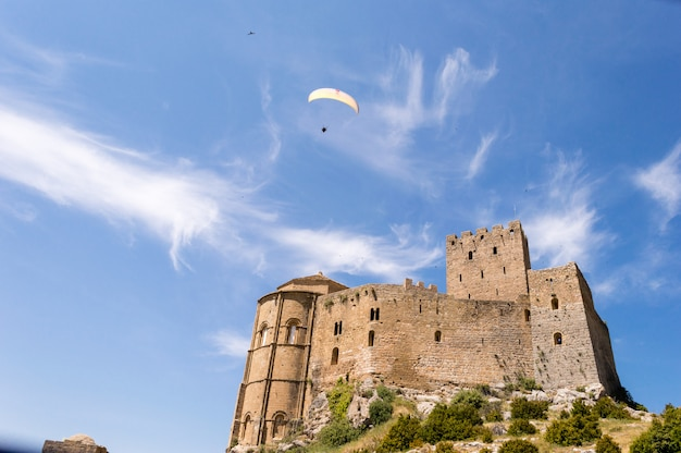 Paragliding in the sky. paragliders flying over the medieval castle of loarre, huesca, spain Premium Photo
