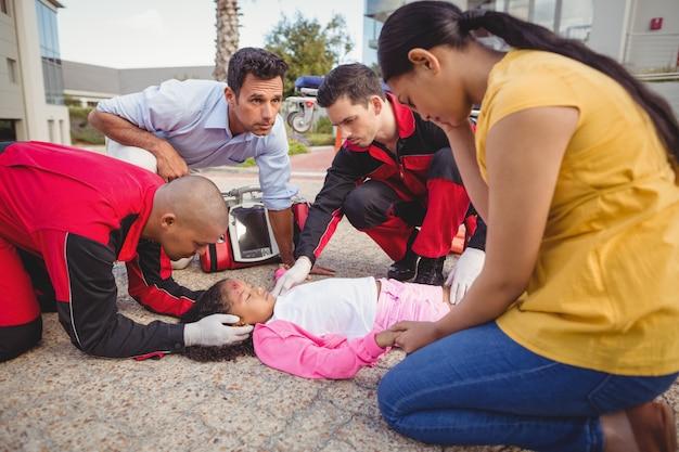 Paramedici che esaminano la ragazza ferita Foto Gratuite