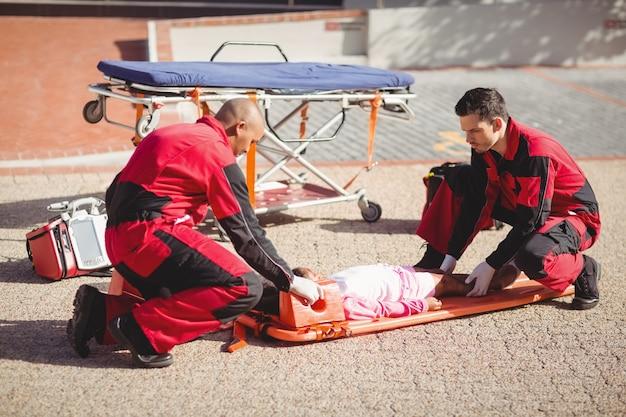 I paramedici che mettono la ragazza ferita su un tabellone Foto Gratuite