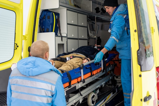 Paramedics in uniform pushing stretcher with fixed unconscious man into ambulance car to get him to hospital Premium Photo