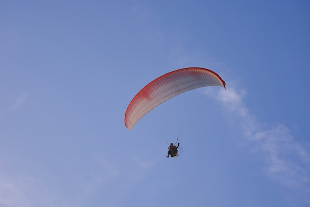 Paramotor (powered paraglider) with red-white parachute flying in sky, extreme sport. Premium Photo